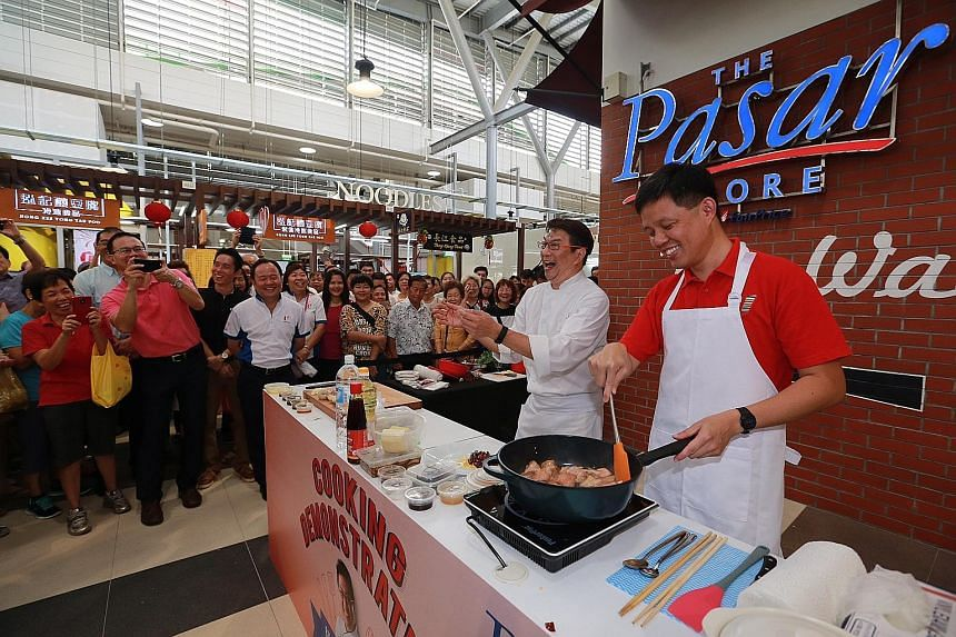 Mr Chan (in red) and chef Eric Teo at the official opening of Bukit Panjang Hawker Centre and Market. The food stalls are open at least six days a week and 12 hours a day to ensure that there are enough dining options for residents in the area.