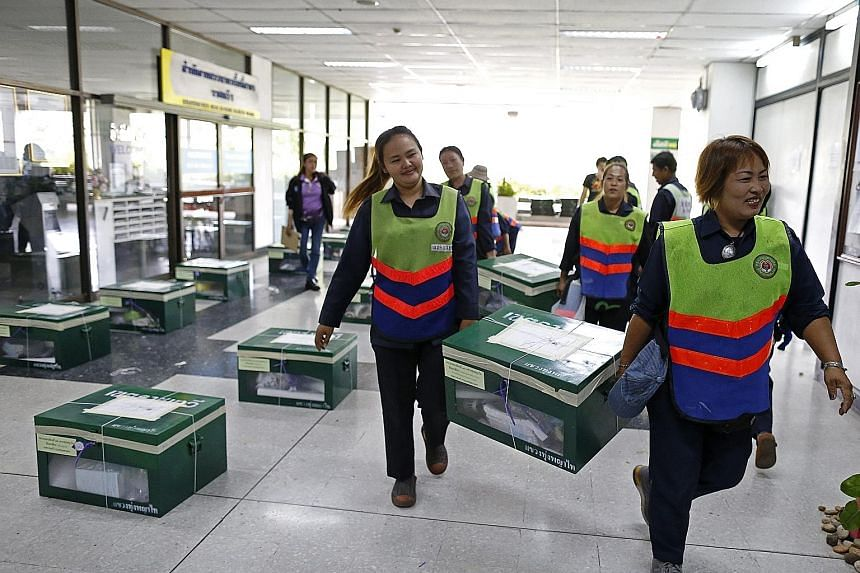 Thai workers in Bangkok carrying ballot boxes in preparation for today's vote on a draft Constitution. Several embassies, including Singapore's, have urged their nationals to take precautions during the referendum.