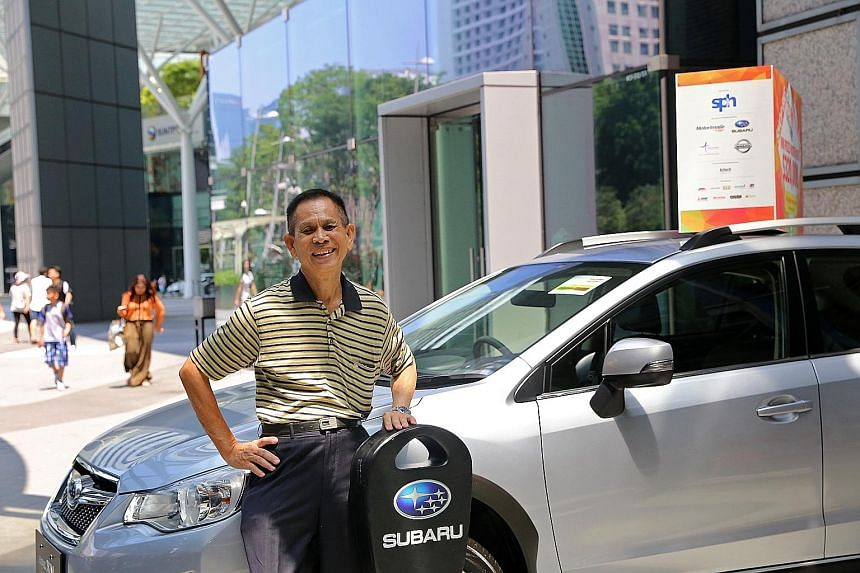 Retiree Tay Say Lian (left) with his new Subaru XV 1.6i-S, which he won at the first draw. In the second draw, SAF regular Goh Yew Boon won a Nissan Sylphy 1.8L.