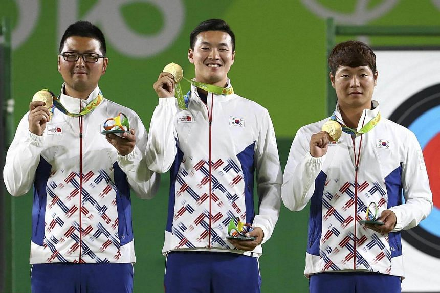 (From left) South Korea's Kim Woo-Jin, Ku Bon-Chan and Lee Seung-Yun pose on the podium after winning the gold medal.