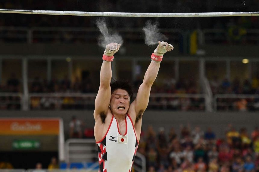 Japan's Kohei Uchimura falls while competing in the qualifying for the men's horizontal bar event.