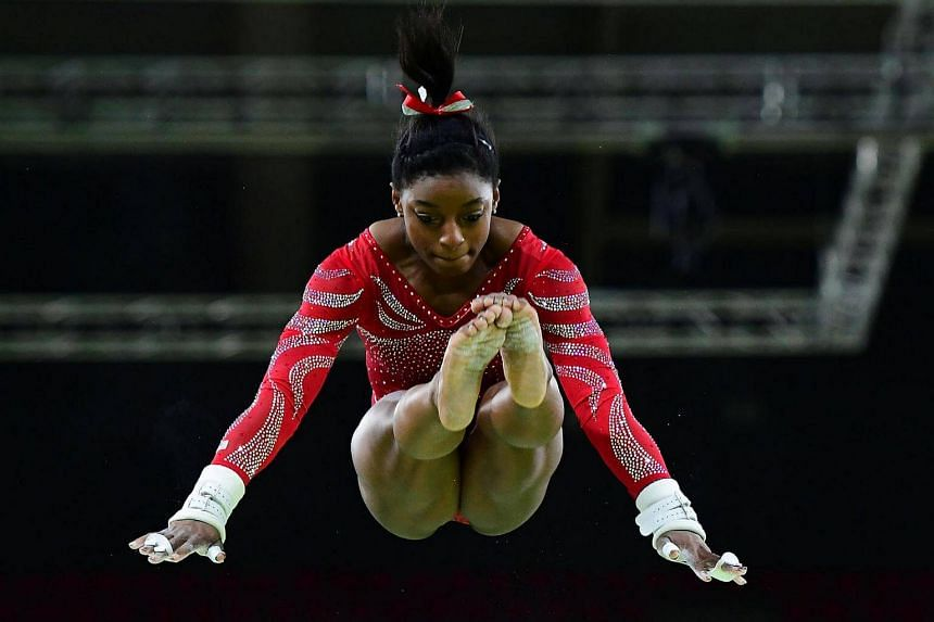 US gymnast Simone Biles practices on the uneven bars of the women's Artistic gymnastics at the Olympic Arena on August 4.