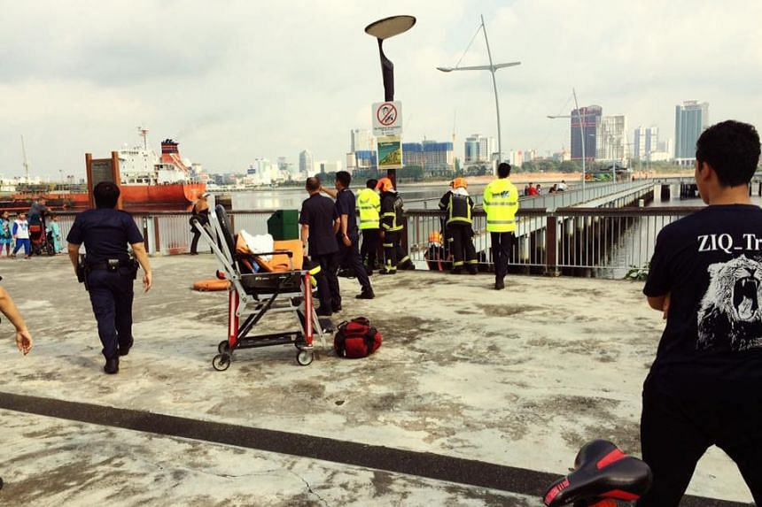 SCDF personnel and police officers at the Woodlands Waterfront jetty where the body of a woman was found floating in the water.