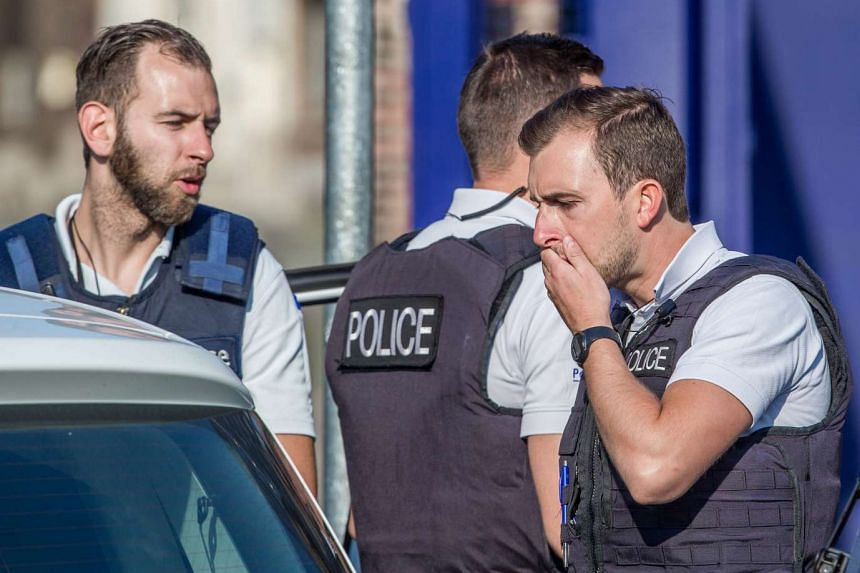 Belgian police officers oversee the scene of the attack.