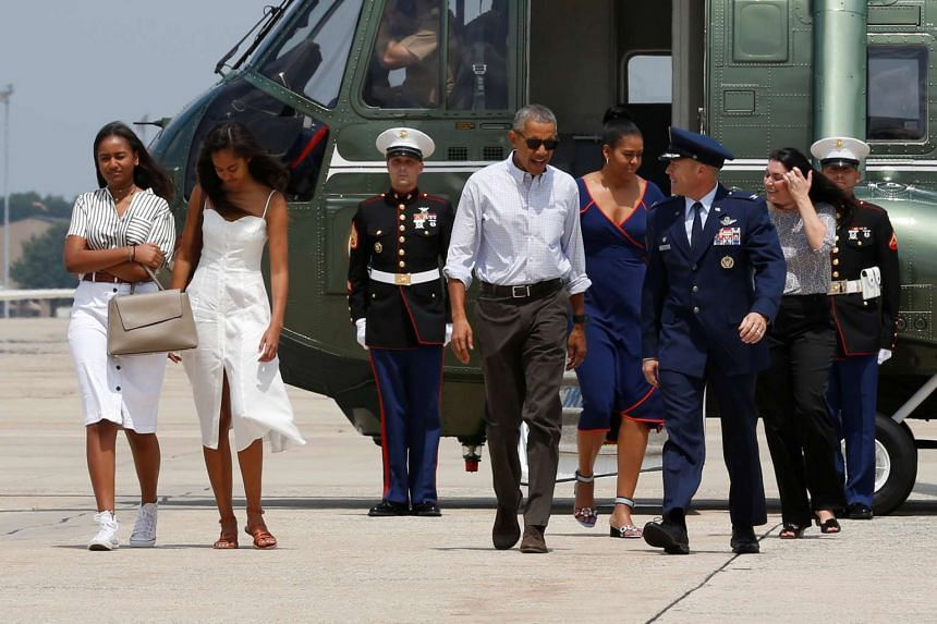 US President Barack Obama (centre) and his family arrive to board Air Force One for travel to Massachusetts for their annual vacation at Martha's Vineyard.