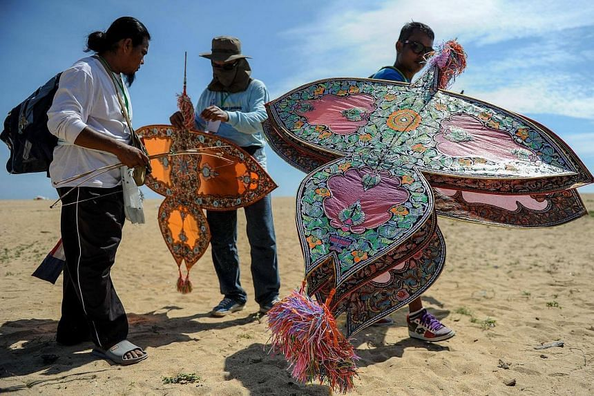Participants carry their traditional Malaysian kites known as Wau Jala Budi during the annual kite festival at Pantai Genting beach in Tumpat on the outskirts of Kota Bharu, Malaysia's northeastern Kelantan state on June 2.