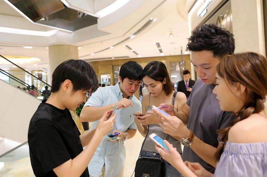 Thai tourists engrossed in the Pokemon Go game while at Ion Orchard.