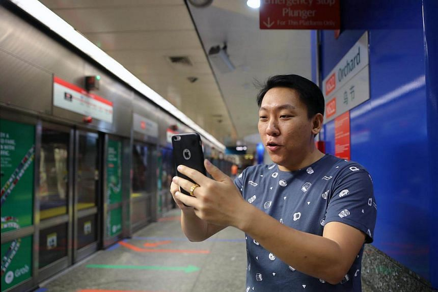 Pokemon Go player Kenji Lee, 31, trying to catch a pokemon at Orchard MRT station.