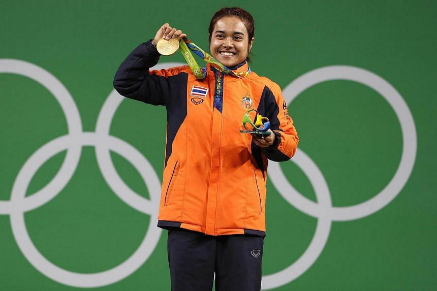 Sopita Tanasan of Thailand holds up her gold medal for the women's 48kg category of the Rio 2016 Olympic Games Weightlifting events at the Riocentro in Rio de Janeiro, Brazil, on August 6.