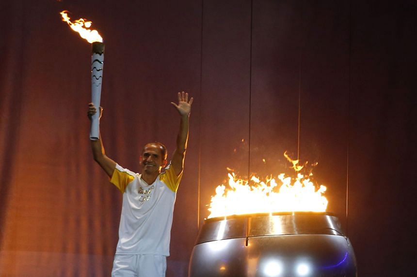 Former marathoner Vanderlei de Lima lighting the Olympic cauldron during Friday's opening ceremony at the Maracana Stadium. He competed at Athens 2004 where he was accosted by a priest 6km from the finish but still took third spot.