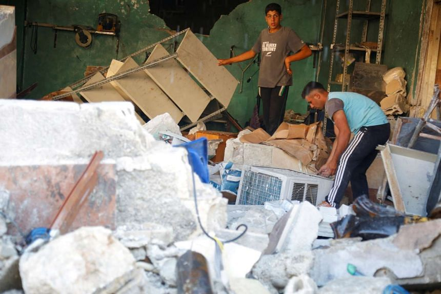 Men inspect rubble after an airstrike on a hospital in the town of Meles, western Idlib city in rebel-held Idlib province, Syria Aug 6, 2016.