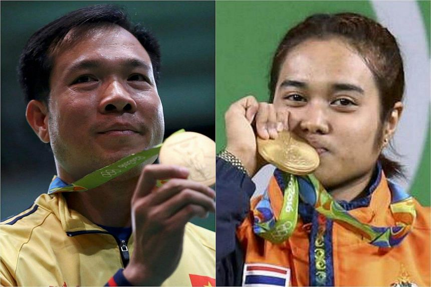 Vietnamese shooter Hoang Xuan Vinh (left) and Thai weightlifter Sopita Tanasan.
