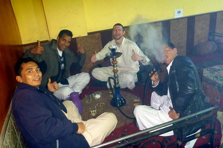 This photograph received from Irish tourist Jonny Blair on August 6 shows Jonny Blair (centre, right) drinking tea and smoking shisha with three Afghan companions in Mazar-i-Sharif during his travels in Afghanistan.