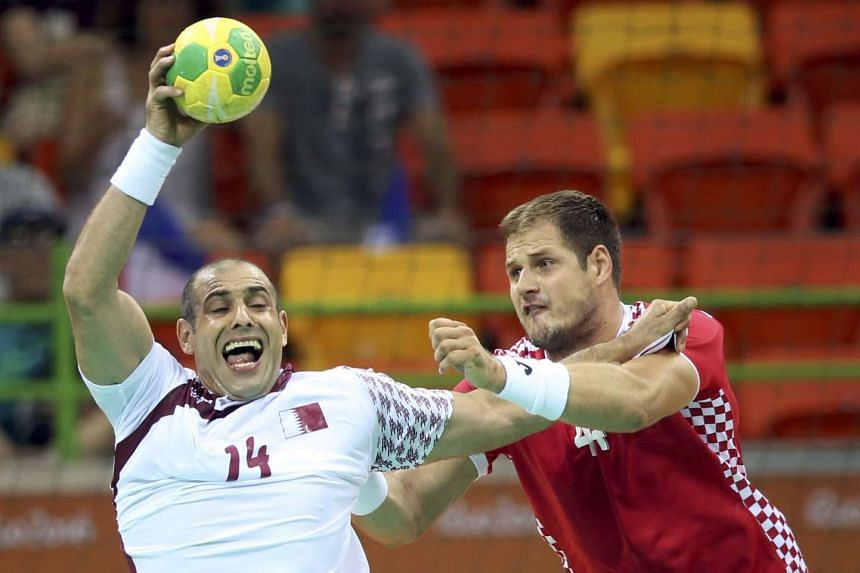 Bassel Alrayes (left) of Qatar and Kresimir Kozina of Croatia in action at the men's preliminary Group A match at the Future Arena on Aug 7, 2016.