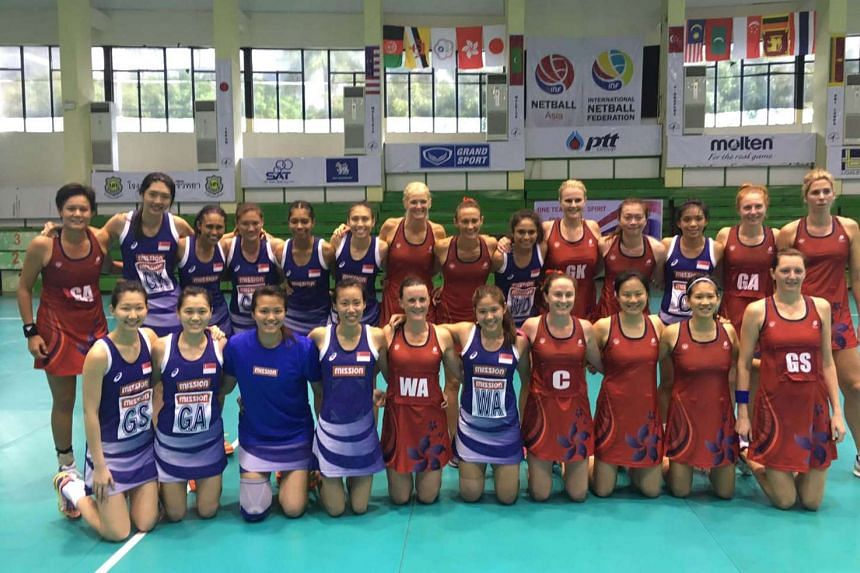 The Singapore netball team taking a group photo with the Hong Kong netball team. Singapore netted the bronze medal at the Asian Netball Championship on August 7.