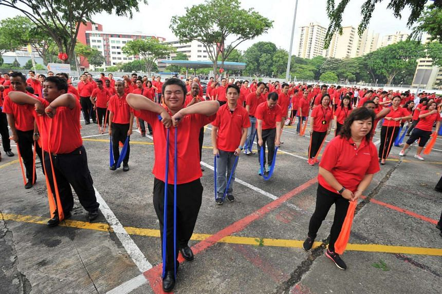ComfortDelGro staff seen stretching their way into Singapore's largest ever mass workout with resistance bands on Aug 8.