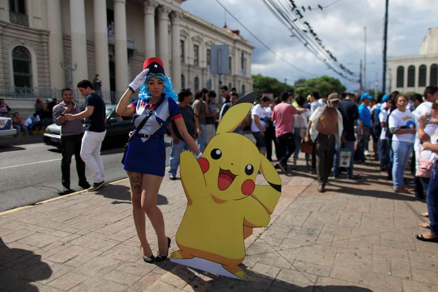 A cosplayer dressed as a character of Pokemon Go participates in a poketour organised by the municipality in San Salvador, El Salvador, on July 23, 2016.