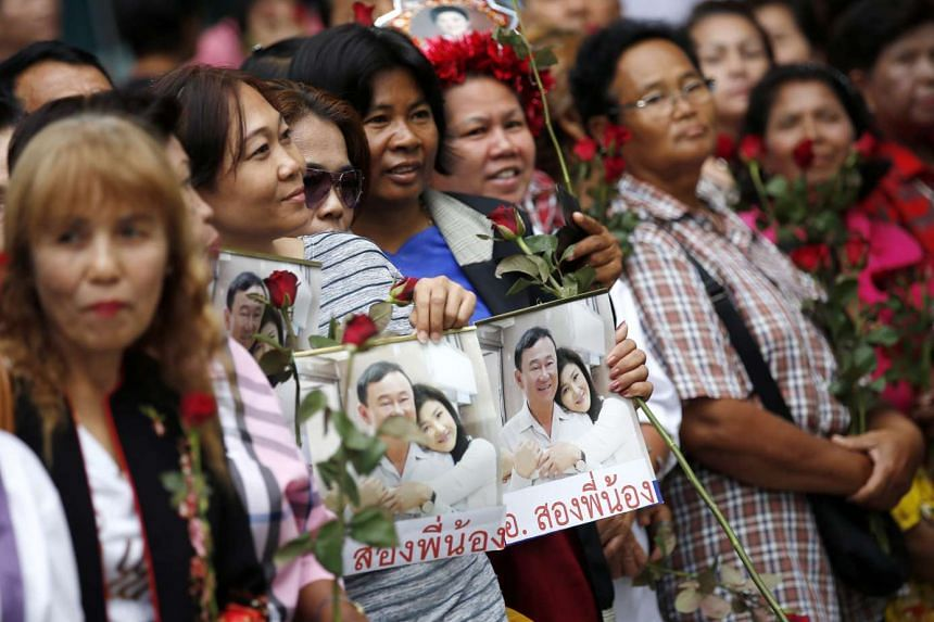 Supporters of former Yingluck Shinawatra hold pictures of her and her brother Thaksin Shinawatra at the Supreme Court in Bangkok, on Aug 5, 2016.