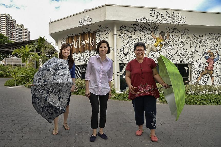 From left: Ms Jacelyn Lim, deputy executive director of Autism Resource Centre, Ms Kho and Ms Loy. The umbrellas feature floral designs by Jolie, who also did the Art Faculty's mural in the background.
