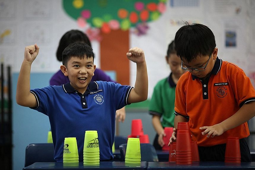 Primary 4 classmates Lance Paglinawan (left) and Matthew Tan from Meridian Primary having a go at cup stacking.