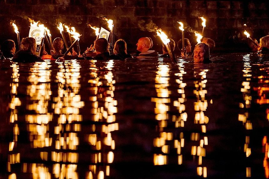Torch swimmers forming an almost surreal tableau in Maschsee Lake in Hannover, Germany, on Saturday. About 130 swimmers plunged into the traditional torchlight swim that is an integral part of the annual lakeside festival.