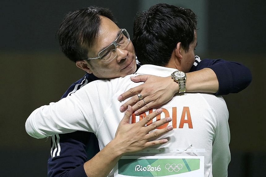 New Olympic 10m air pistol champion Hoang Xuan Vinh, who edged out Brazil's Felipe Wu, is congratulated by eighth-placed Indian Jitu Rai.