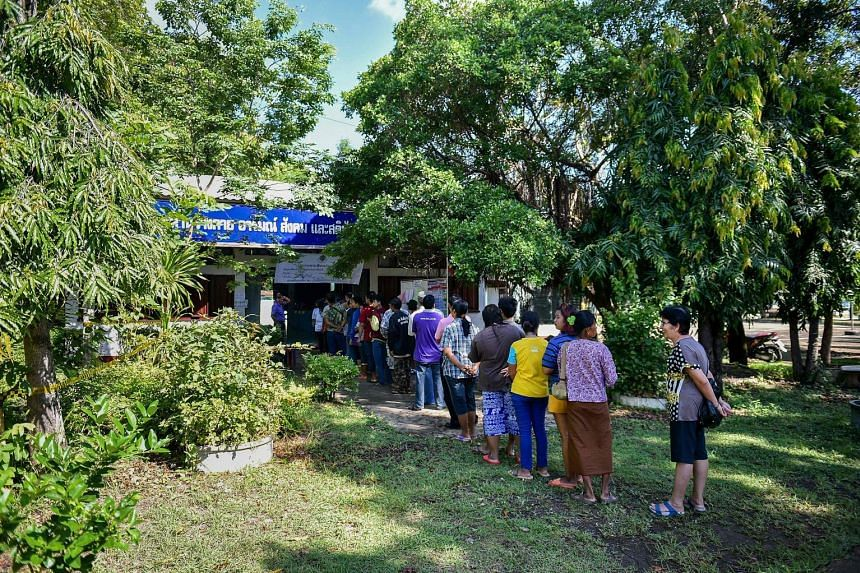 Thai PM Prayut Chan-o-cha (top) and former prime minister Yingluck Shinawatra (above) casting their vote in Bangkok. People queuing at a polling station in Thailand's north-eastern province of Buriram yesterday to vote in the country's constitutional