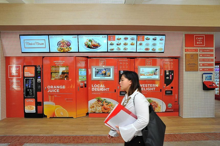 """Mr Jing Quek of Konbini with a """"vending oven"""", which maintains a temperature of 60 to 70 deg C, optimal for slow cooking food. A raw egg put into the machine, for example, comes out soft-boiled. At the VendCafe in Block 320C Anchorvale Drive are (fro"""