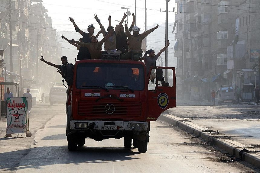 Syrian civil defence volunteers celebrating in the northern city of Aleppo last Saturday after breaking a government siege on Syria's second city.