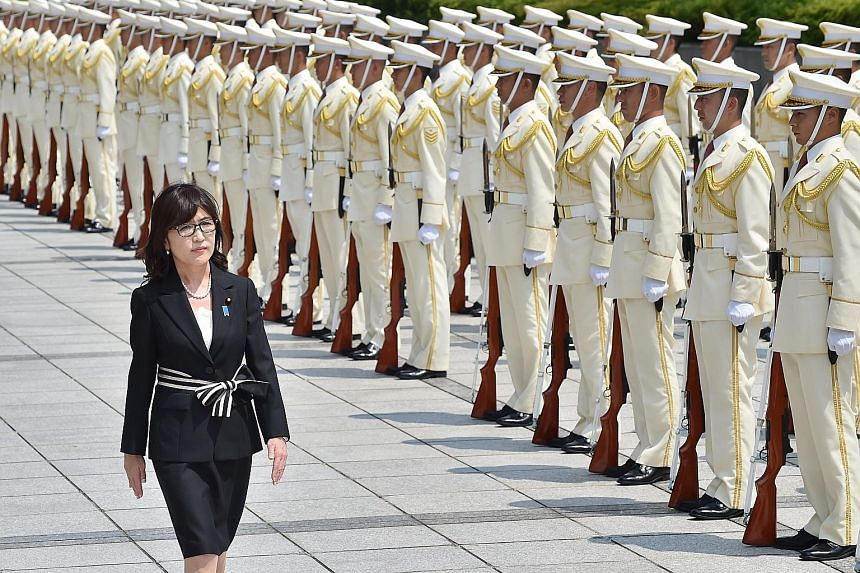 Ms Tomomi Inada reviewing an honour guard in her new capacity as Japan's Defence Minister last Thursday.