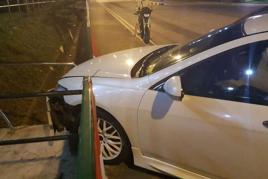 The white Honda sedan crashed into a railing after its driver attempted to overtake another car.