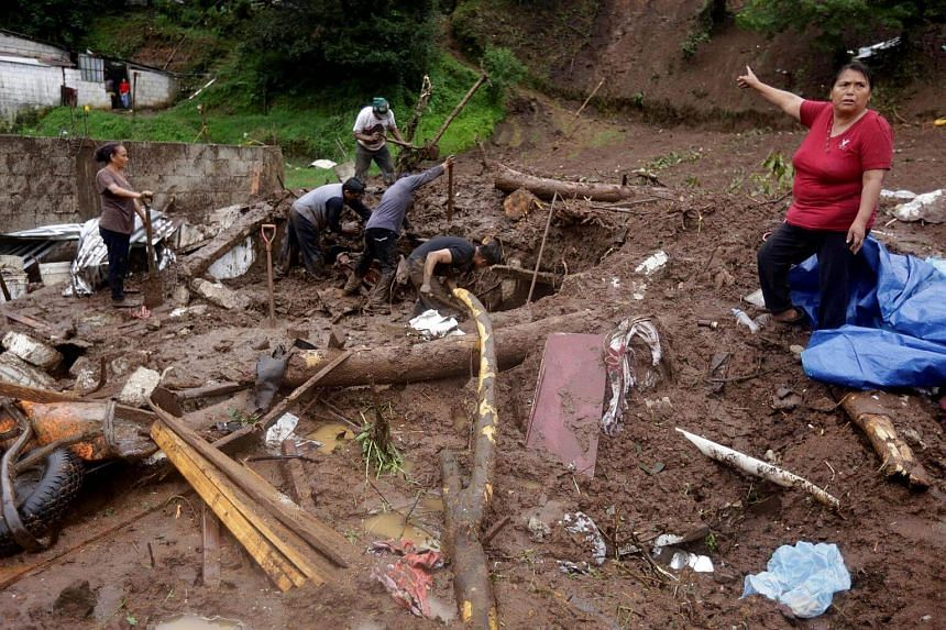 A woman gestures as residents shovel to recover belongings from their house damaged after a mudslide following heavy showers caused by the passing of Tropical Storm Earl, in the town of Huauchinango, in Puebla state, Mexico, on August 7.