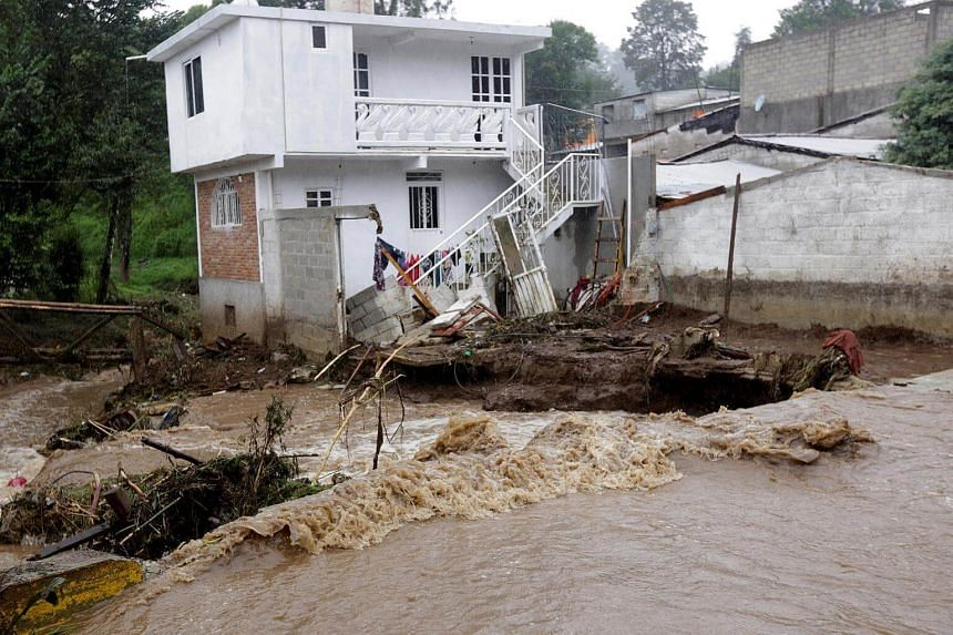 A house damaged after a river overflowed its banks following heavy showers caused by the passing of Tropical Storm Earl, in the town of Huauchinango, in Puebla state, Mexico, on August 7.