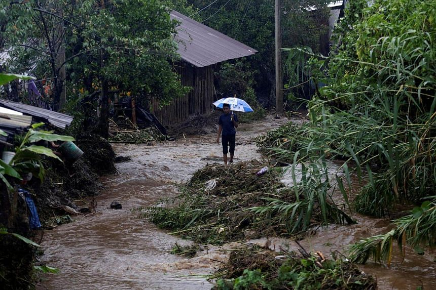 A child holds an umbrella as he walks by an area affected by heavy showers caused by the passing of Tropical Storm Earl, in the town of Huauchinango, in Puebla state, Mexico, on August 7.