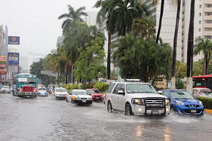 A general view shows vehicles transiting at a flooded street due to heavy rains left by Tropical Storm Earl's passage in Acapulco, Mexico, on August 6.