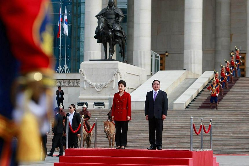 South Korea's President Park Geun-hye (centre, left) stands with Mongolia's President Tsakhiagiin Elbegdorj during a welcoming ceremony for Park in Ulan Bator on July 17.