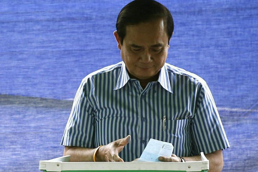 Thai Prime Minister Prayut Chan-o-cha casts his ballot during a referendum for the new constitution at a polling station in Bangkok, Thailand on August 7.