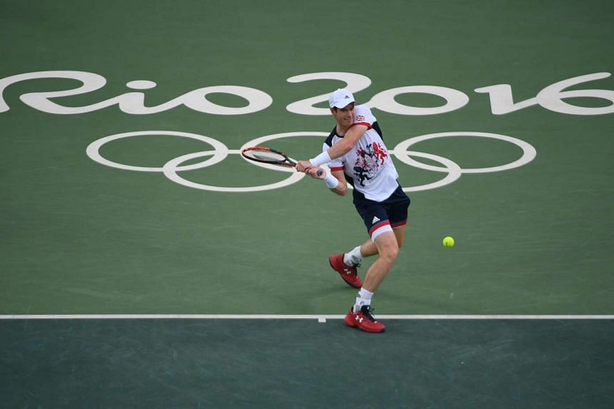 Britain's Andy Murray returns the ball to Serbia's Viktor Troicki during their men's first round singles tennis match at the Olympics on Sunday.