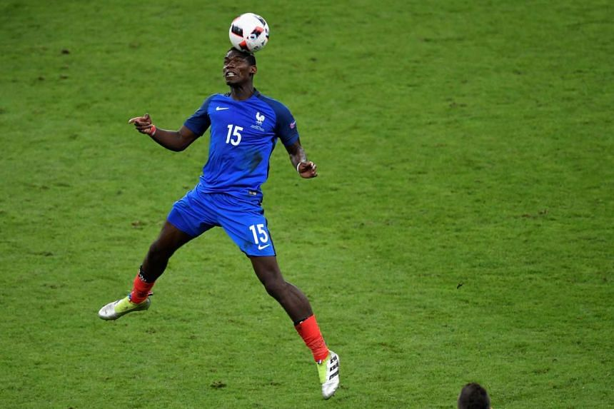 France's midfielder Paul Pogba heads the ball during the Euro 2016 final football match.