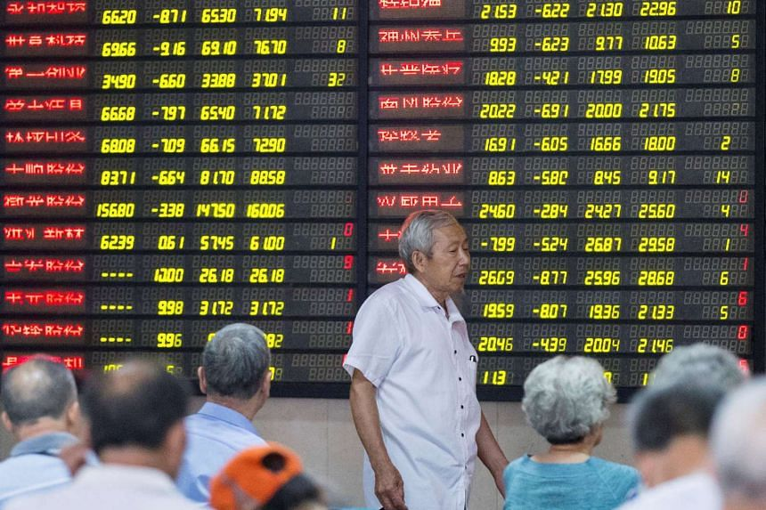 An investor walks past an electronic board showing stock information at a brokerage house in Nanjing, Jiangsu province, on July 27, 2016.