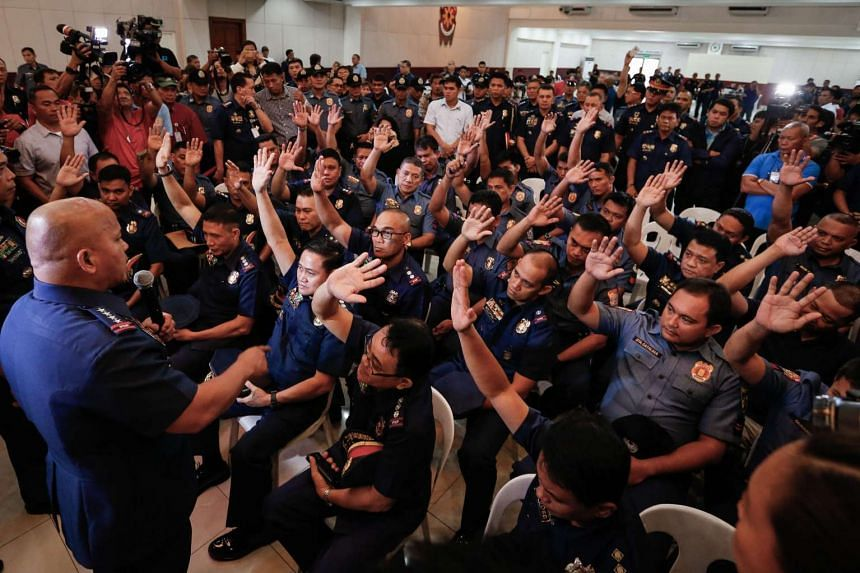 Filipino police officers allegedly involved in the illegal drug trade raise their hands at Camp Crame in Quezon City, on Aug 8, 2016.