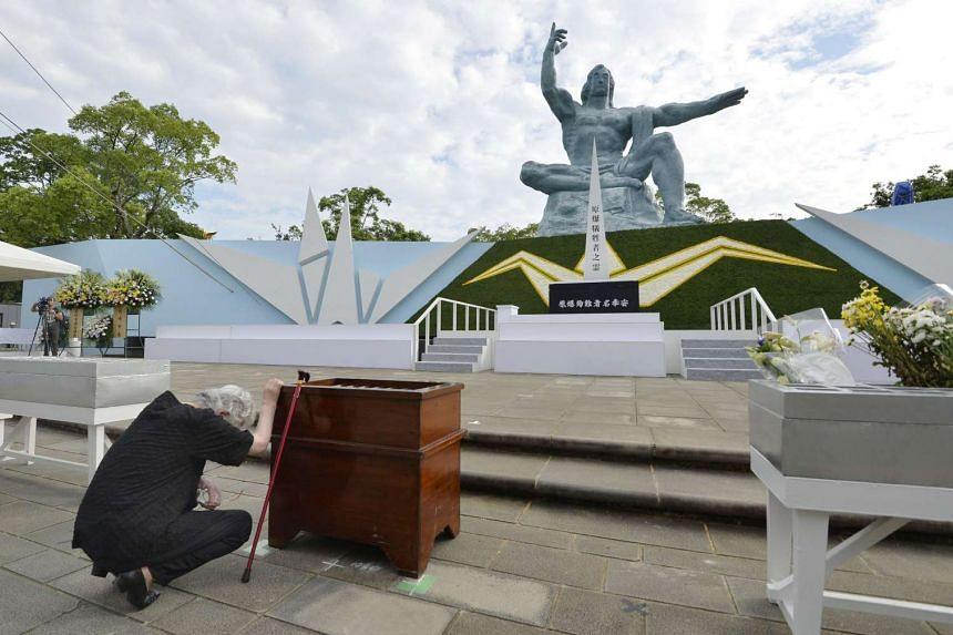 A woman reacts in front of the Peace Statue on the anniversary of the 1945 atomic bombing in Nagasaki at Nagasaki's Peace Park on Aug 9, 2016.