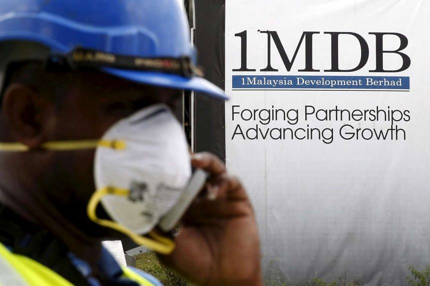 A construction worker talks on the phone in front of a 1Malaysia Development Berhad (1MDB) billboard.