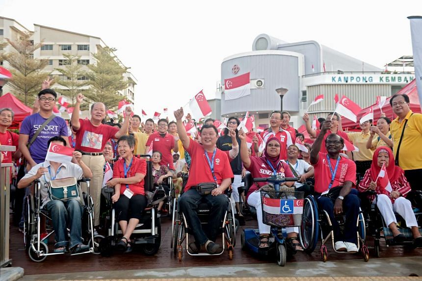 Members of Singapore Hua Yuan Hui (in wheelchairs) and members of the public cheer before the flag-off for the brisk walk.
