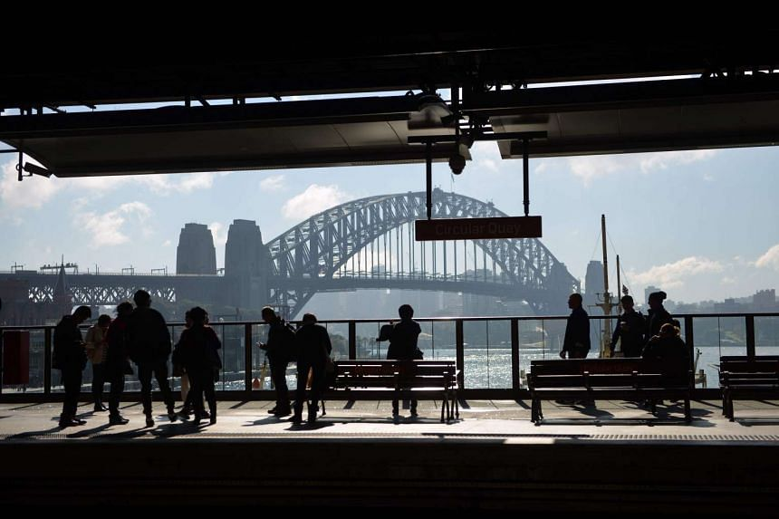 People wait for a train at Circular Quay near the harbour in Sydney on July 5, 2016.