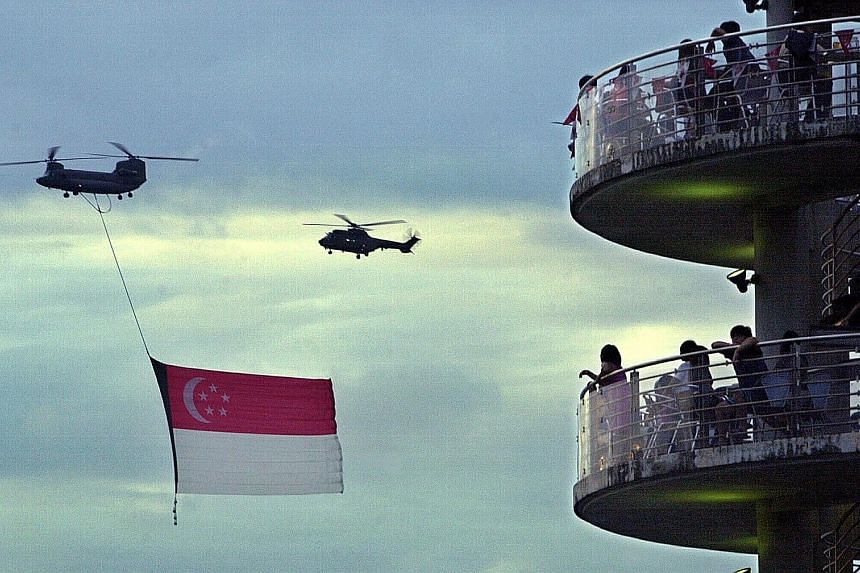 Spectators viewing the fly-past of the state flag at the Tanjong Rhu lookout tower in 2001. They were treated to a spectacular fireworks finale.