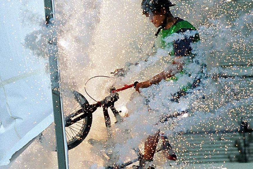 BMX stunt biker Hiruan Ahmad, 19, performing a daredevil act at the pre-parade segment in 1999 (above); an SAF commando gliding down amid a burst of light and smoke from the top of the National Stadium's 60m light towers the same year; and Lt-Col (NS) Cle