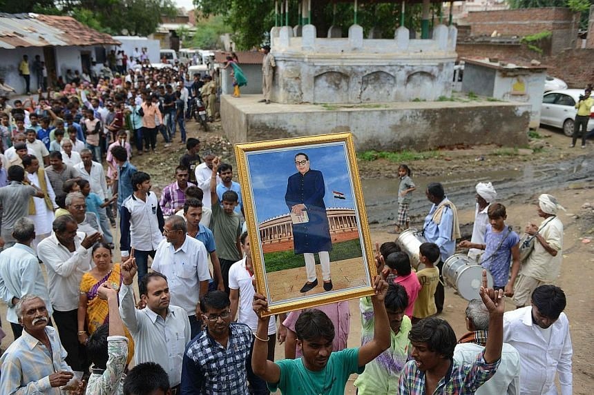 A supporter of the Dalit community holding up a picture of social reformer B. R. Ambedkar during a march in Mr Modi's home state of Gujarat to protest against the recent attack on four Dalit villagers.