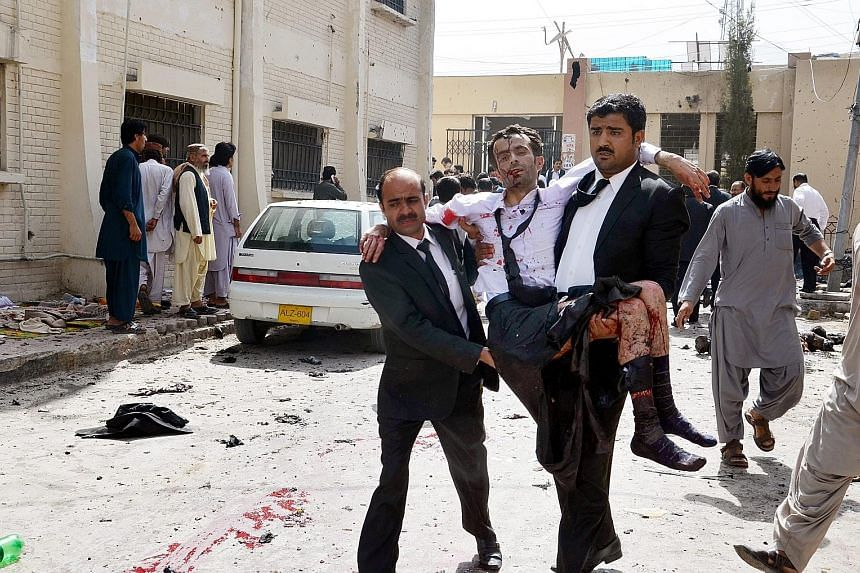 An injured man being carried away after a suicide bomber targeted a hospital in Pakistan's violence-plagued south-western province of Balochistan. The bomber struck after about 200 people had gathered at the hospital after the fatal shooting of a sen