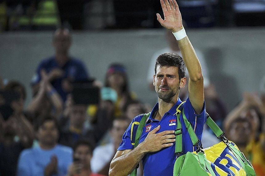 An overcome Novak Djokovic leaves the court on Sunday after his unexpected straight-sets loss in the first round to Argentina's Juan Martin del Potro, who had also beaten him at London 2012.